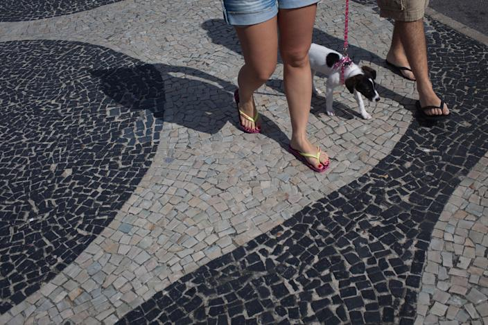In this July 17, 2012 photo, a couple wearing Havaianas sandals walk their dog along Copacabana beach in Rio de Janeiro, Brazil. In Brazil, literally everyone wears Havaianas, the now world-famous brand of rubber and plastic flip-flops that's celebrating its 50th birthday this year. (AP Photo/Felipe Dana)