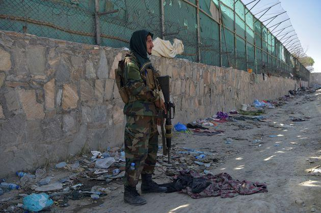 A Taliban fighter stands guard at the site of the August 26 twin suicide bombs, which killed scores of people including 13 US troops, at Kabul airport on August 27, 2021 (Photo: WAKIL KOHSAR via Getty Images)