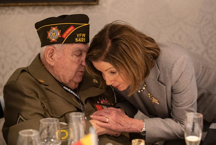 Speaker of the House Nancy Pelosi leans in close to George Merz to better hear what he is saying while attending a luncheon Dec. 14, 2019, for the 75th anniversary of the Battle of the Bulge.