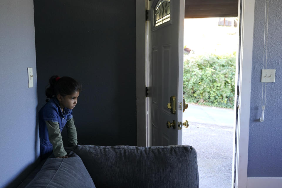 One of the four children of Abdul (not shown), who worked as a mechanic before he left Kabul, Afghanistan with his family about a month ago, peers out from a staircase, Thursday, Sept. 16, 2021, in the rental house the family has been provided as a place to stay in Seattle. The home is owned by Thuy Do, who was nine years old when her family arrived in the United States from Vietnam in the 1980s. Now Do and her husband have offered their vacant rental home to refugee resettlement groups to house newly arriving Afghans in need of a place to stay. (AP Photo/Ted S. Warren)
