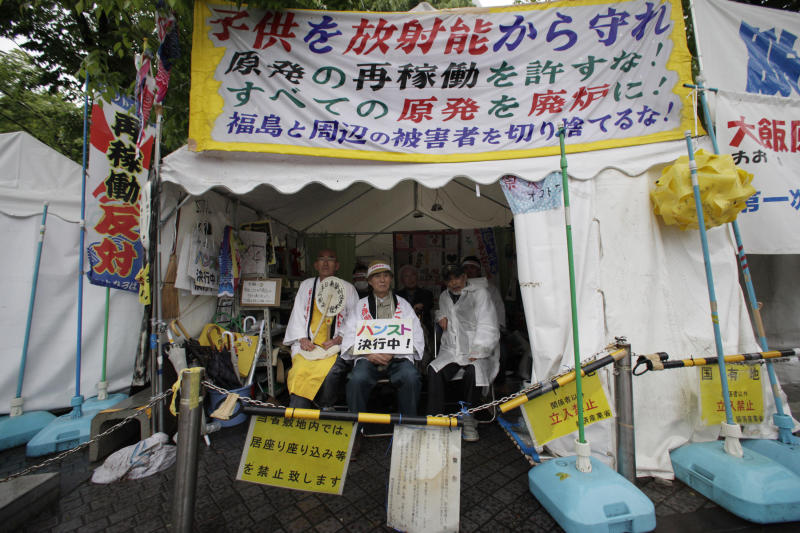 FILE - In this May 3, 2012 file photo, anti-nuclear activists, Taro Fuchigami, right, Taichi Masakiyo, center, and an unidentified Buddhist monk, stage a hunger strike in a tent in front of Japan's Economy, Trade and Industry Ministry in Tokyo against the government's plan to restart the Oi nuclear power plant in western Japan. The Fukushima crisis is eroding years of Japanese efforts to reduce greenhouse gas emissions blamed for global warming, as power plants running on oil and natural gas fill the electricity gap left by now-shuttered nuclear reactors. Japan will be free of atomic power for the first time since 1966 on Saturday, May 5, when the last of its 50 usable reactors is switched off for regular inspections. The central government would like to restart them at some point, but it is running into strong opposition from local citizens and governments. (AP Photo/Shizuo Kambayashi, File)