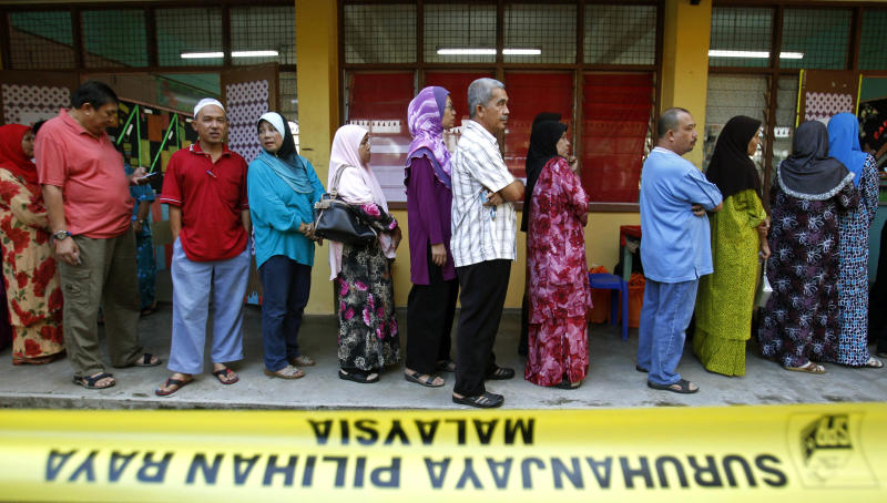 Malaysian voters wait in a line to cast their ballots in the general elections at a polling station in Pekan, Pahang state, Malaysia, Sunday, May 5, 2013. Malaysians have begun voting in emotionally charged national elections that could see the long-ruling coalition ousted after nearly 56 years in power. (AP Photo/Lai Seng Sin)
