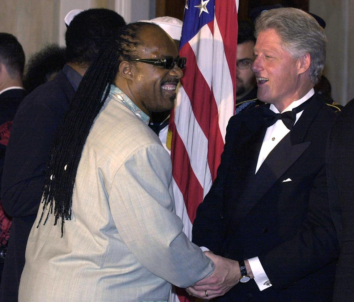 U.S. President Bill Clinton welcomes singer Stevie Wonder for a White House State Dinner held in honor of [South African President Thabo Mbeki], May 22. More than 200 politicians, entertainers and diplomats attended the dinner under a tent on the South Lawn. (REUTERS/Mike Theiler)