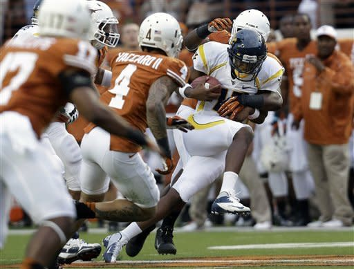 West Virginia quarterback Geno Smith, right, runs with the ball as Texas defends during the first quarter of an NCAA college football game on Saturday, Oct. 6, 2012, in Austin, Texas. (AP Photo/Eric Gay)