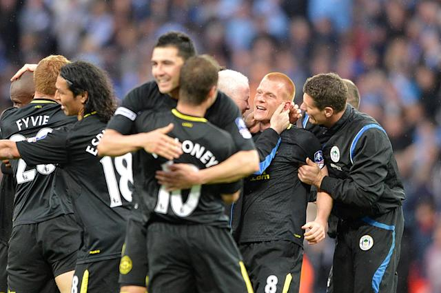 Wigan Athletic's Ben Watson (second right) is mobbed by team-mates and staff, after the final whistle