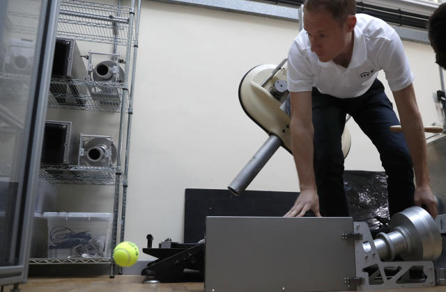 In this photo taken Friday June, 28, 2019, Jamie Caple-Davies, the head of the International Tennis Federation science and technical department, shows off a machine that tests the surface of a tennis court, during an interview with the Associated Press, at the International Tennis Federation (ITF) lab in Roehampton, near Wimbledon south west London. Based for about 20 years in a three-room area on what used to be a pair of squash courts in Roehampton, the ITF tech lab is filled with more than $1 million worth of machines that help make sure rules are followed and parameters are met. (AP Photo/Alastair Grant)