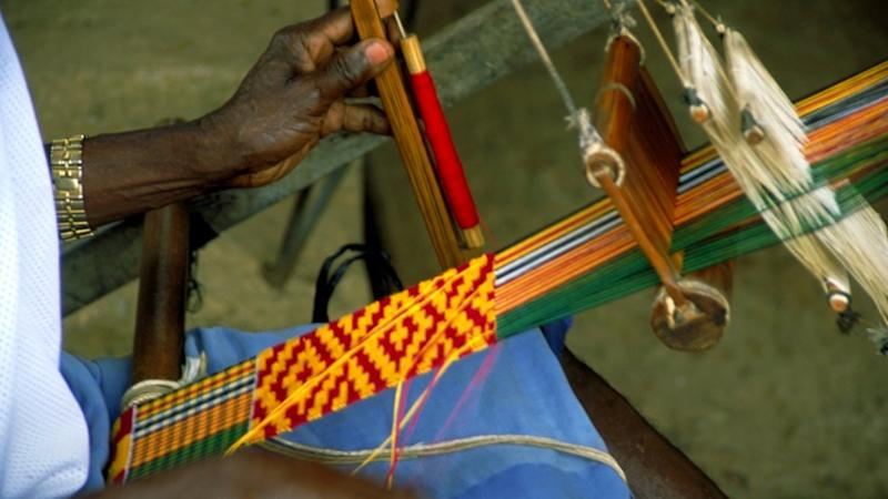 Person weaving kente