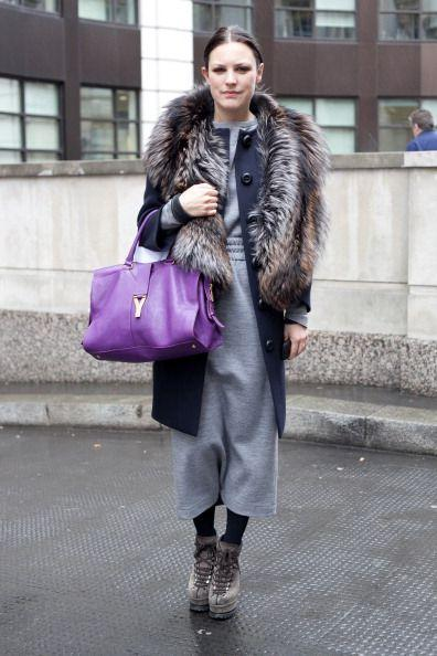 <p>This bright purple satchel offsets the 50 shades of grey in this sweater dress, long peacoat, fur piece, and booties.</p>