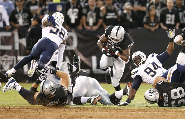 Oakland Raiders running back Darren McFadden (20) runs against San Diego Chargers linebacker Donald Butler (56) and defensive tackle Corey Liuget (94) during the first quarter of an NFL football game in Oakland, Calif., Monday, Sept. 10, 2012. (AP Photo/Tony Avelar)