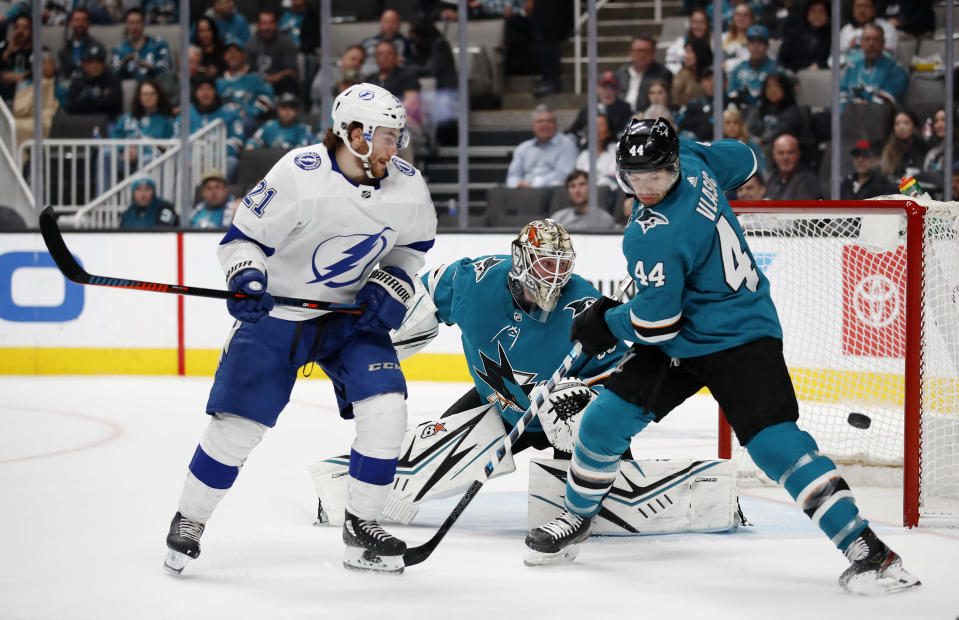 Tampa Bay Lightning center Brayden Point and San Jose Sharks goaltender Aaron Dell (30) and defenseman Marc-Edouard Vlasic (44) looks watch the puck during the second period of an NHL hockey game in San Jose, Calif., Saturday, Feb. 1, 2020. (AP Photo/Josie Lepe)