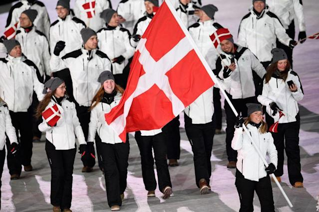 <p>Denmark's flag bearer Elena Moller Rigas leads the delegation as they parade wearing minimalsitic white winter jackets, black pants, and gray beanies during the opening ceremony of the 2018 PyeongChang Games. (Photo: Martin Bureau/AFP/Getty Images) </p>