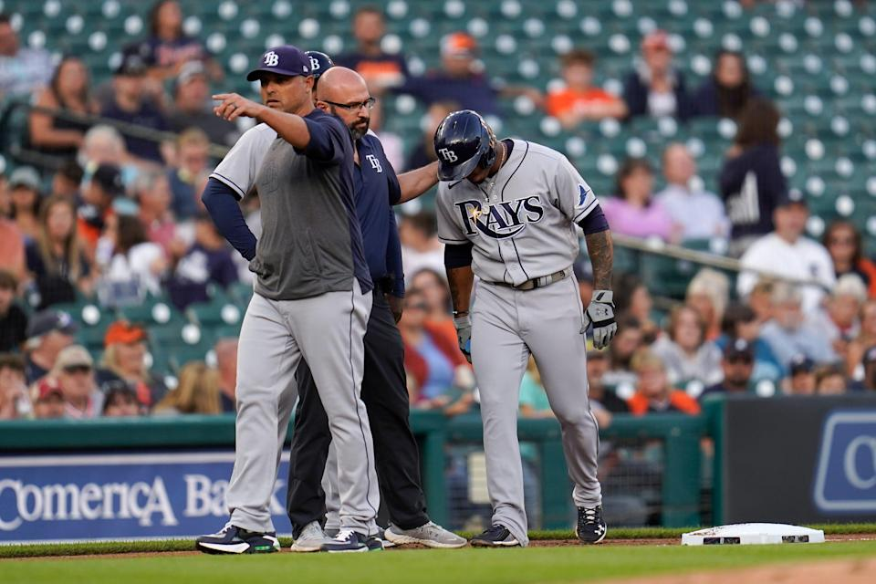 Rays manager Kevin Cash, from left, signals for a pinch runner as team trainer Joe Benge helps shortstop Wander Franco to the dugout from third base against the Tigers in the first inning on Friday, Sept. 10, 2021, at Comerica Park.