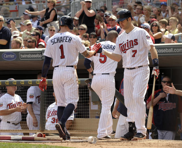 Minnesota Twins' Joe Mauer (7) greets teammates Eduardo Escobar, center, and Jordan Schafer (1) at their dugout after they scored during the third inning of a baseball game against the Detroit Tigers in Minneapolis, Sunday, Aug. 24, 2014. (AP Photo/Tom Olmscheid)