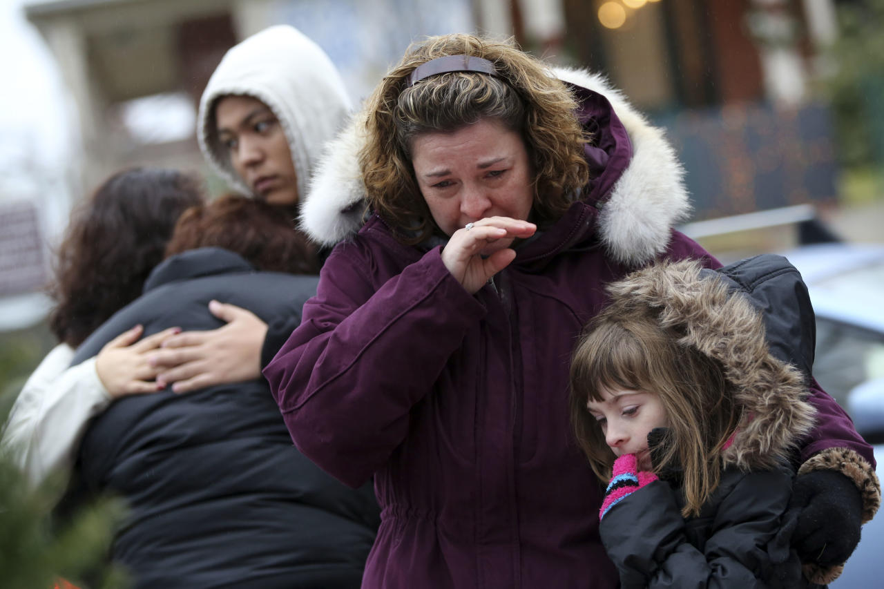 Mourners grieve at one of the makeshift memorials for victims of the Sandy Hook Elementary School shooting, Sunday, Dec. 16, 2012, in Newtown, Conn. On Friday, a gunman allegedly killed his mother at their home and then opened fire inside the school, killing 26 people, including 20 children. (AP Photo/Mary Altaffer)