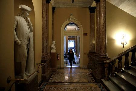 A woman walks past a statue of Benjamin Franklin after President Donald Trump and the U.S. Congress failed to reach a deal on funding for federal agencies on Capitol Hill in Washington
