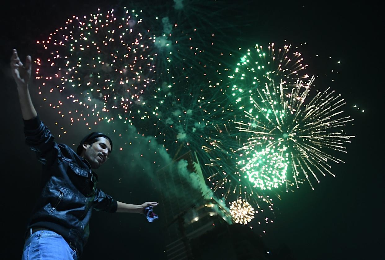 A Pakistani man dances on a street next to fireworks as he celebrates the new year in the port city of Karachi early on January 1, 2018. (Photo: ASIF HASSAN via Getty Images)