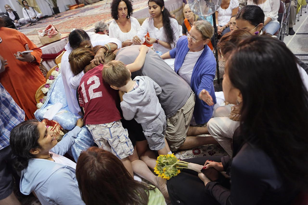 """Mata Amritanandamayi, also known as """"The Hugging Saint"""" embraces a family on July 10, 2012 in New York City. The Hindu spiritual leader and guru is on a 10-city U.S. tour, where she is expected to bless thousands of people individually at free public """"darshan"""" gatherings. Amritanandamayi, 58, from India's southern state of Kerala, is considered a living saint by her followers, who refer to her as """"Amma"""" or mother. She has been giving the public """"darshan"""" gatherings for 35 years, with the aim of bringing good fortune, well-being and grace to her followers through her embrace. Participants are encouraged to donate to her global charitable organizations, known collectively as """"Embracing the World.""""  (Photo by John Moore/Getty Images)"""