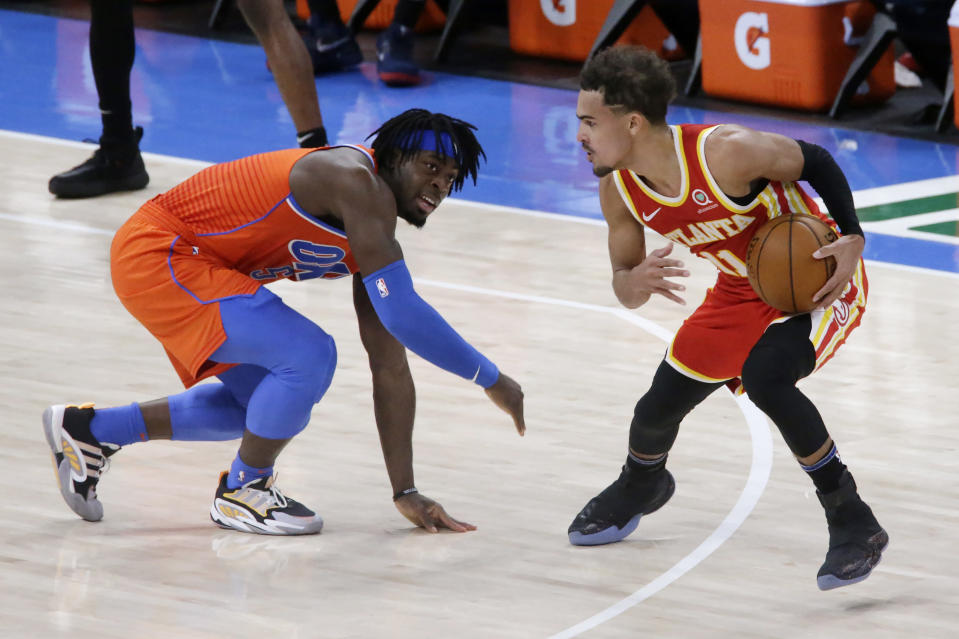 Atlanta Hawks guard Trae Young (11) is defended by Oklahoma City Thunder forward Luguentz Dort during the first half of an NBA basketball game Friday, Feb. 26, 2021, in Oklahoma City. (AP Photo/Garett Fisbeck)
