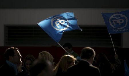 People's Party (PP) supporters wave flags during a campaign rally in Las Rozas