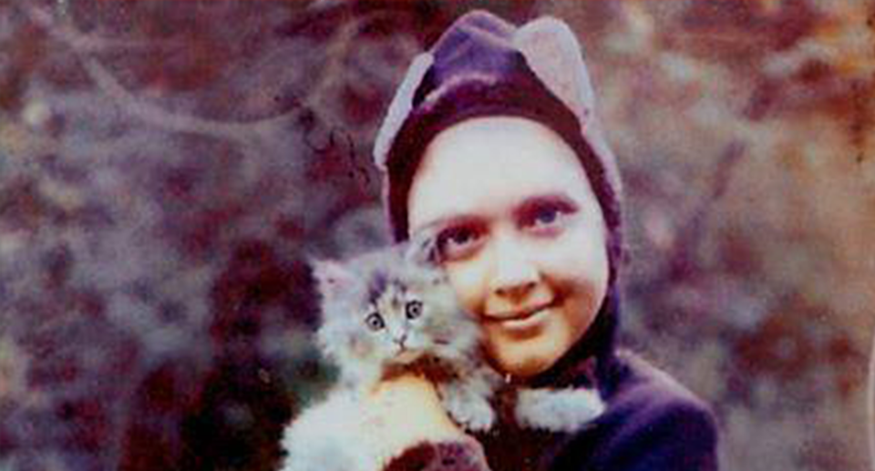 A young Carole Baskin dressed as a cat and holding a cat.