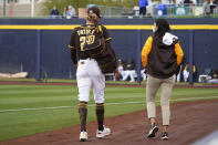 San Diego Padres' Fernando Tatis Jr., left, walks off the field following an injury in the third inning of a spring training baseball game against the Cincinnati Reds Tuesday, March 23, 2021, in Peoria, Ariz. (AP Photo/Sue Ogrocki)