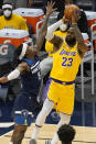 Los Angeles Lakers' LeBron James (23) shoots as Minnesota Timberwolves' Jarred Vanderbilt (8) defends in the first half of an NBA basketball game, Tuesday, Feb. 16, 2021, in Minneapolis. (AP Photo/Jim Mone)