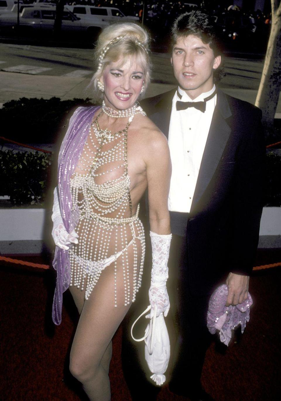 """<p>Not to be outdone, actress Edy Williams showed off some serious skin at the awards ceremony. Williams is perhaps better known for her <a href=""""https://en.wikipedia.org/wiki/Edy_Williams"""" rel=""""nofollow noopener"""" target=""""_blank"""" data-ylk=""""slk:outrageous awards show outfits"""" class=""""link rapid-noclick-resp"""">outrageous awards show outfits</a> than she is for her acting career. </p><p><strong>RELATED:</strong> <a href=""""https://www.goodhousekeeping.com/beauty/fashion/news/a48064/katy-perry-naked-versace-dress-oscars-2018/"""" rel=""""nofollow noopener"""" target=""""_blank"""" data-ylk=""""slk:Katy Perry Wore the Most Naked Dress at the 2018 Oscars"""" class=""""link rapid-noclick-resp"""">Katy Perry Wore the Most Naked Dress at the 2018 Oscars</a></p>"""