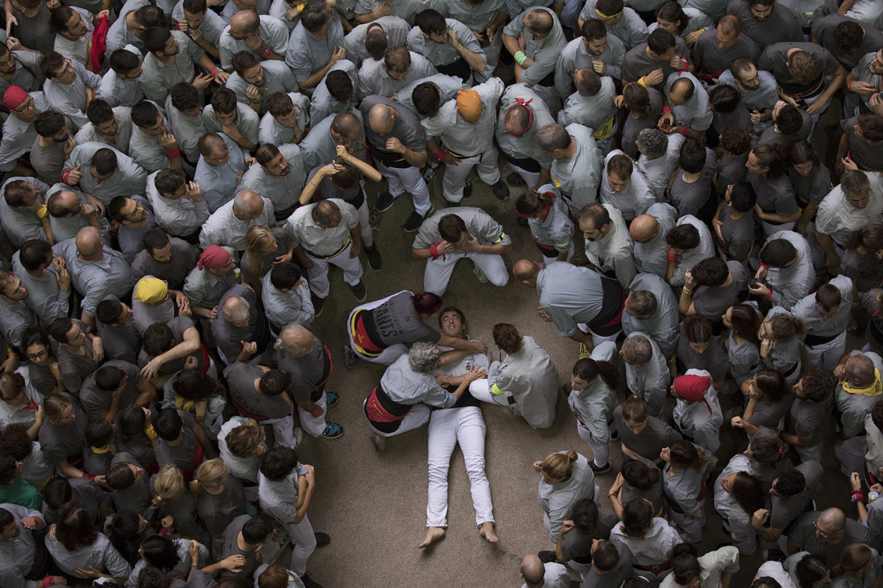 """<p>A member of """"Castellers de Sants"""" waits for medical assistance after being injured during their human tower during the 27th Human Tower Competition in Tarragona, Spain, on Oct. 7, 2018. (Photo: Emilio Morenatti/AP) </p>"""