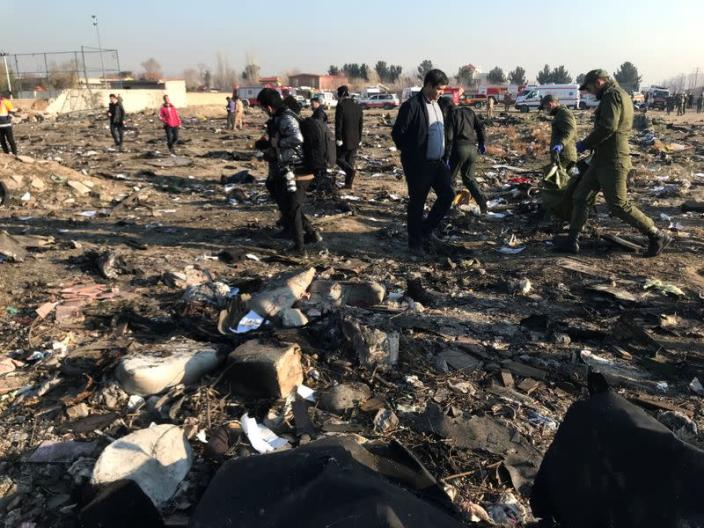 Rescue team members with people check the debris from a plane crash belonging to Ukraine International Airlines after take-off from Iran's Imam Khomeini airport, on the outskirts of Tehran