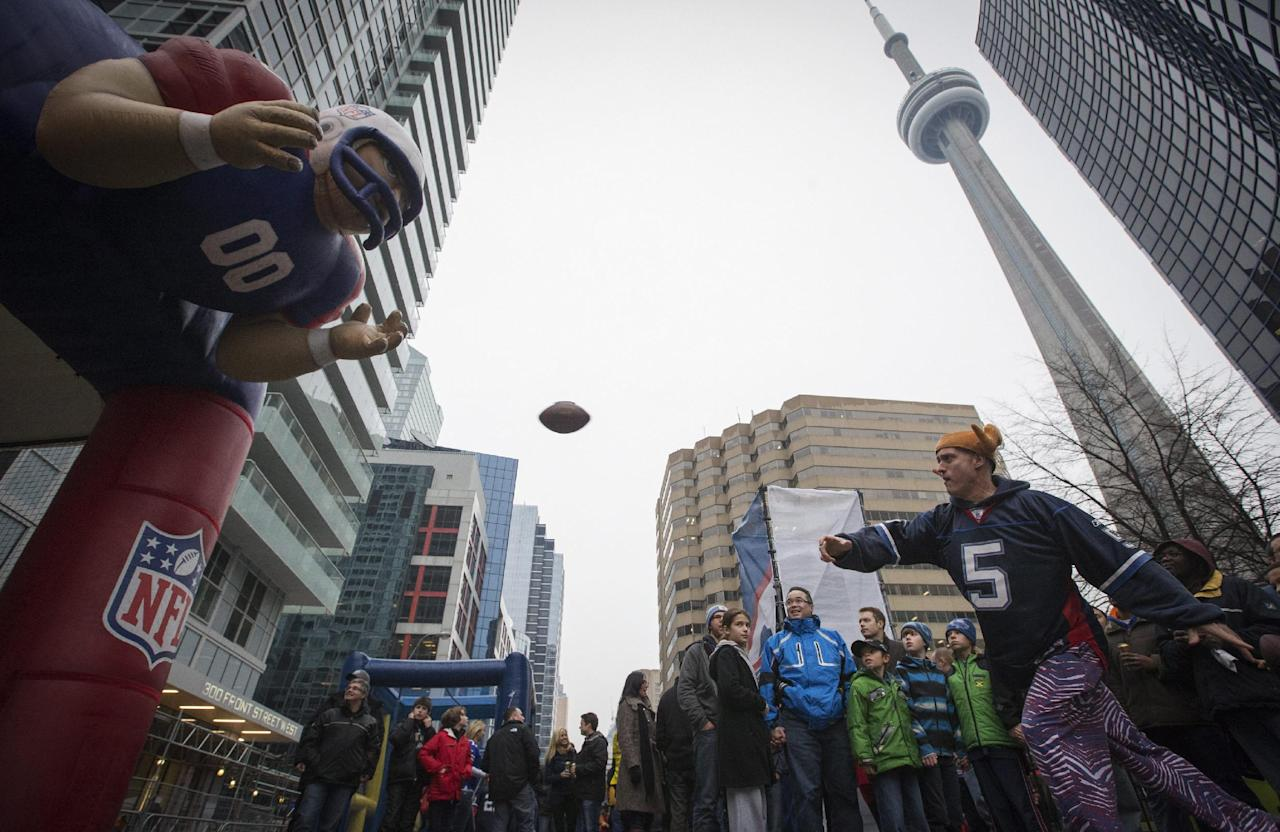 A man throws a football at the tailgate party on Front Street before the Buffalo Bills play the Atlanta Falcons in NFL football action in Toronto, Sunday Dec. 1, 2013. (AP Photo/The Canadian Press, Mark Blinch)