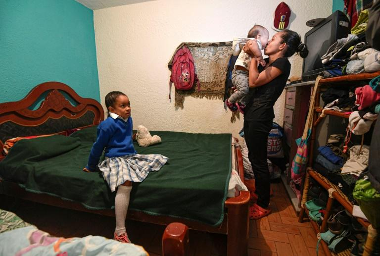 Venezuelan Yisela Palencia holds her baby Wilbelys next to her eldest daughter at their home in Bogota