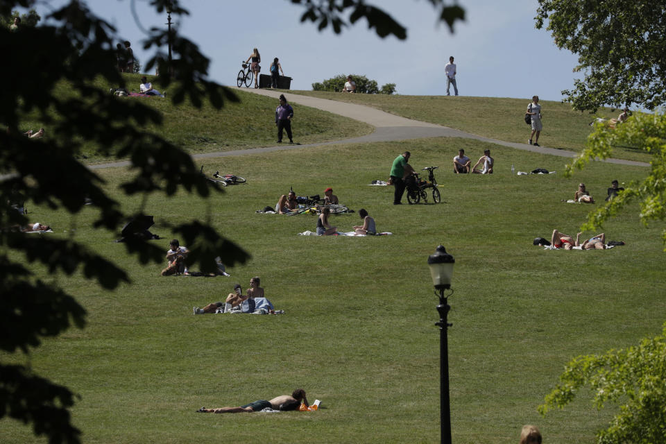 People relax during warm weather on Primrose Hill, in London, Wednesday, May 20, 2020. Lockdown restrictions due to the coronavirus outbreak have been relaxed allowing unlimited outdoor exercise and activities such as sunbathing. The UK's Met Office said Wednesday, it is the hottest day of the year so far with 27.8 Celsius recorded at Heathrow. (AP Photo/Matt Dunham)