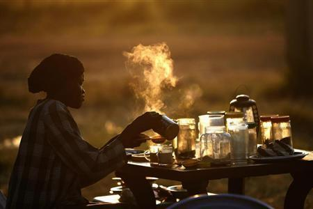 A woman prepares tea at an outdoor coffee shop near a polling station located in a school during a referendum in the town of Abyei