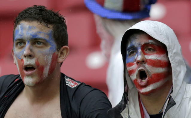 Rain soaked supporters cheer the USA team before the group G World Cup soccer match between the United States and Germany at the Arena Pernambuco in Recife, Brazil, Thursday, June 26, 2014. (AP Photo/Julio Cortez)