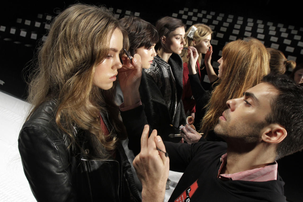 """FILE - In this Feb. 15, 2012, file photo, models have their make-up finalized under runway light before the J. Mendel Fall 2012 collection is modeled during Fashion Week, in New York. The 19 editors of Vogue magazines around the world made a pact to project the image of healthy models. They agreed to """"not knowingly work with models under the age of 16 or who appear to have an eating disorder"""" and they will ask casting directors to check IDs at photo shoots, fashion shows and for ad campaigns, according to a Conde Nast International announcement Wednesday.(AP Photo/Richard Drew, file)"""