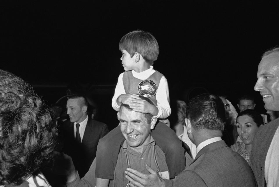 FILE - In this April 19, 1970 file photo, Apollo 13 astronaut Jim Lovell carries his son, Jeff, 4, on his shoulders as he arrived at Ellington Air Force Base in Houston. (AP Photo)