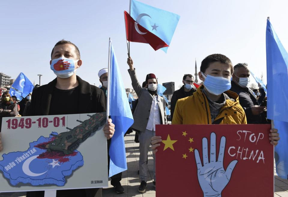 Uyghurs hold banners in a protest against China.