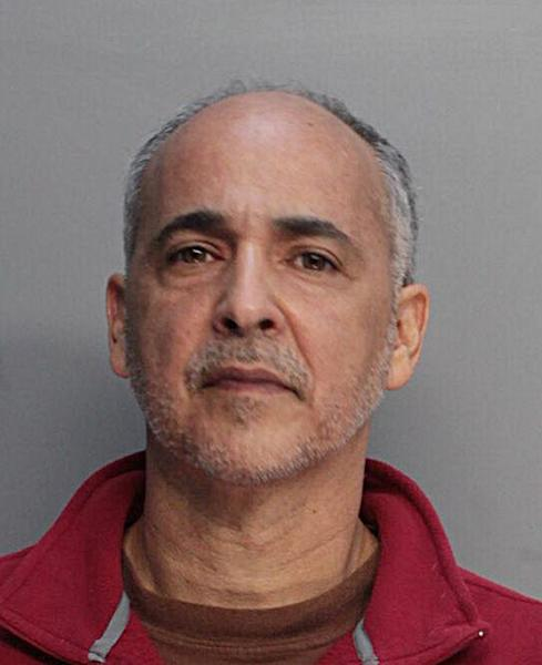 In this police booking mug made available by the Miami Dade Corrections and Rehabilitation Dept., shows artists Maximo Caminero on Sunday, Feb. 16, 2014. Caminero smashed a $1 million vase at Miami's new Perez Art Museum to protest what he called its favoritism for international rather than local art. Caminero was charged with criminal mischief. (AP Photo/Miami Dade Corrections and Rehabilitation Dept, HOPD)