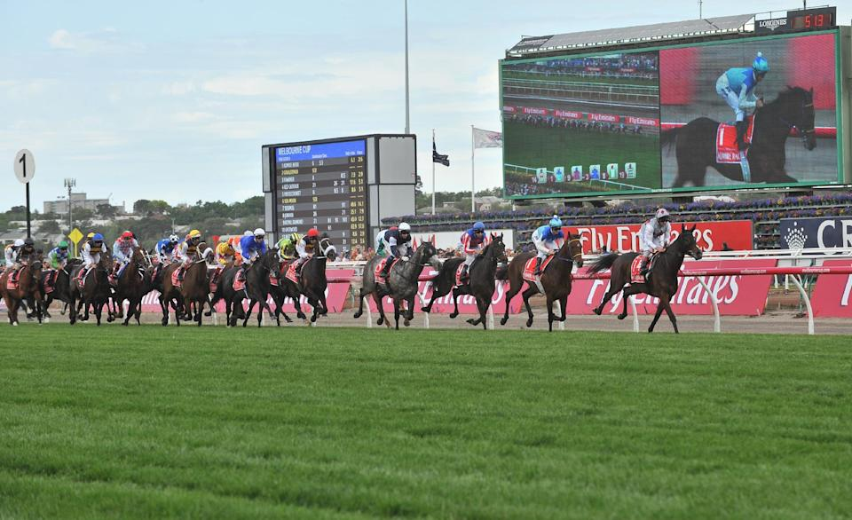 Racing favourite Admire Rakti (2nd R) runs in second place and is displayed on the big screen during the early stages, but finished last at the Melbourne Cup horse race in Melbourne, Australia, on November 4, 2014 (AFP Photo/Paul Crock)