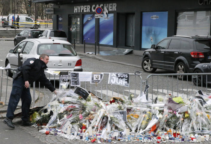 FILE - In this Jan. 12, 2015 file photo, a police officer lays flowers at the site of the kosher market where four hostages were killed and shortly before Israeli Prime Minister Benjamin Netanyahu's visit to the site, in Paris. The January 2015 attacks against Charlie Hebdo and, two days later, a kosher supermarket, touched off a wave of killings claimed by the Islamic State group across Europe. Seventeen people died along with the three attackers. Thirteen men and a woman accused of providing the attackers with weapons and logistics go on trial on terrorism charges Wednesday Sept. 2, 2020. (AP Photo/Francois Mori, File)