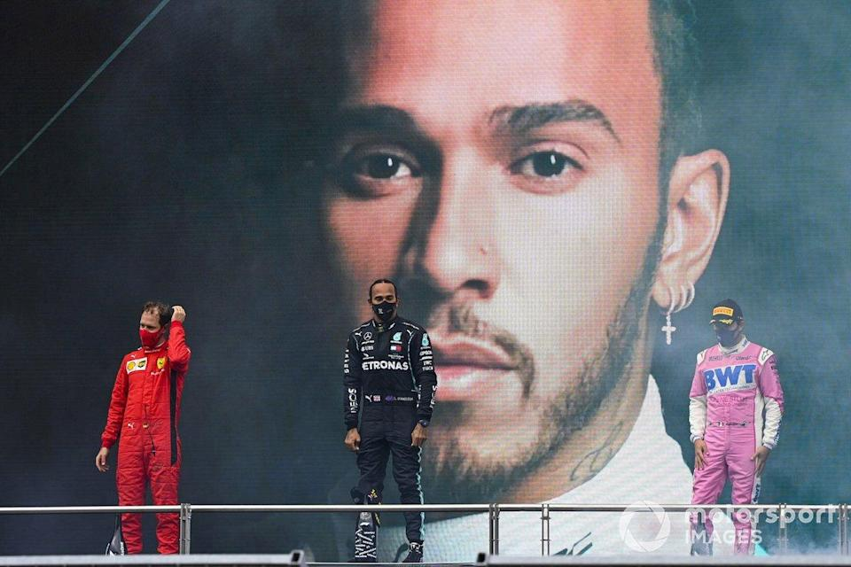 """Lewis Hamilton, Mercedes-AMG F1, on the podium after winning the race, to take his 7th World Championship title, with Sergio Perez, Racing Point, 2nd position, and Sebastian Vettel, Ferrari, 3rd position<span class=""""copyright"""">Mark Sutton / Motorsport Images</span>"""