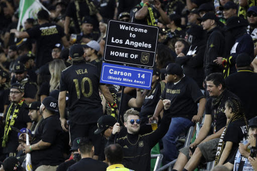 A fan holds a sign during the first half of an MLS soccer match between Los Angeles FC and Los Angeles Galaxy, Sunday, Aug. 25, 2019, in Los Angeles. (AP Photo/Marcio Jose Sanchez)