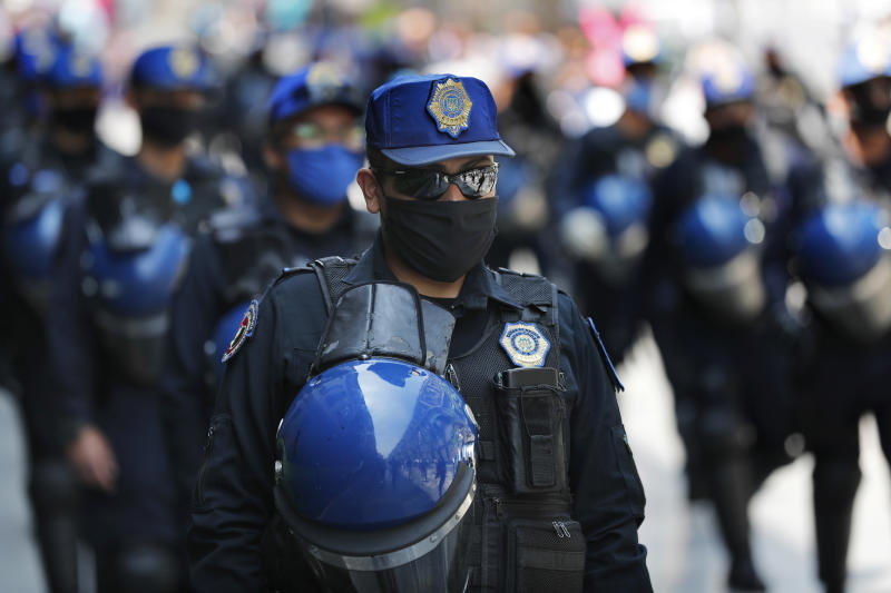 """Police, wearing protective face masks as a precaution against the spread of the new coronavirus, patrol the historic center of Mexico City, Wednesday, April 1, 2020, in an operation to prevent robberies of the businesses that have temporarily closed. Mexico's government has broadened its shutdown of """"non essential activities,"""" and prohibited gatherings of more than 50 people as a way to help slow down the spread of COVID-19. The one-month emergency measures will be in effect from March 30 to April 30. (AP Photo/Marco Ugarte)"""