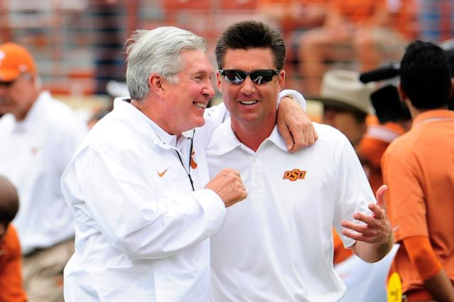 AUSTIN, TX - NOVEMBER 16: Mike gundy, head coach of the Oklahoma State Cowboys, and Mack Brown, head coach the Texas Longhorns, meet at midfield prior to a game at Darrell K Royal-Texas Memorial Stadium on November 16, 2013 in Austin, Texas. Oklahoma State won the game 38-13. (Photo by Stacy Revere/Getty Images)