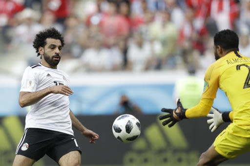 Egypt's Mohamed Salah, left, challenge for the ball with Saudi Arabia goalkeeper Yasser Almosailem during the group A match between Saudi Arabia and Egypt at the 2018 soccer World Cup at the Volgograd Arena in Volgograd, Russia, Monday, June 25, 2018. (AP Photo/Andrew Medichini)