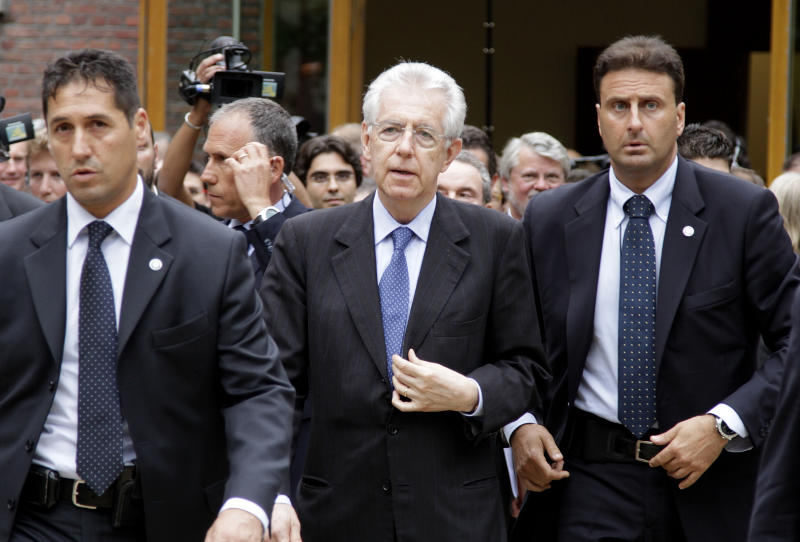 Italian Prime Minister Mario Monti, center, walks with bodyguards as he arrives for a meeting at the Bavarian Representation in Brussels on Wednesday, June 27, 2012. EU leaders will meet for a crucial EU Summit, beginning on Thursday, amid growing concerns over the financial health of Greece, Spain and Italy. (AP Photo/Virginia Mayo)