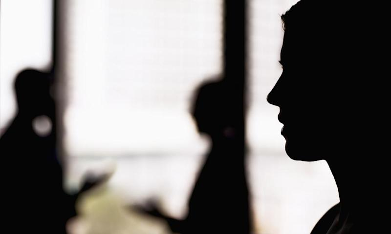A silhouette of a businesswoman with coworkers in the background.