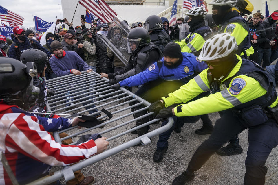 FILE - In this Jan. 6, 2021, file photo violent insurrectionists loyal to President Donald Trump supporters try to break through a police barrier at the Capitol in Washington. A month ago, the U.S. Capitol was besieged by Trump supporters angry about the former president's loss. While lawmakers inside voted to affirm President Joe Biden's win, they marched to the building and broke inside. (AP Photo/John Minchillo, File)