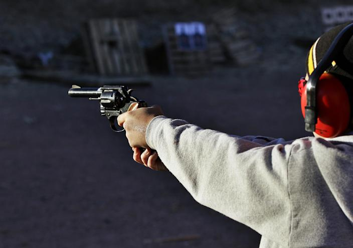 FILE - This Dec. 23, 2012 file photo, a man shoots a revolver, at Dragonman's firing range and gun dealer, outside Colorado Springs, Colo. In an age where it's convenient to do many things online, Colorado legislators are making one less thing possible for people to do from the comfort of their couch: Get a concealed carry permit. A new law requires people to go to a firearm instructor to show they can safely handle a firearm in person before getting a permit, seeking to close what lawmakers say is an Internet-era loophole they didn't envision 10 years ago. (AP Photo/Brennan Linsley, File)