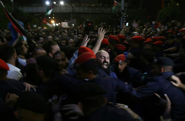 <p>Jordanian security forces scuffle with protesters attempting to breach the area as they stand guard during a demonstration outside the prime minister's office in the capital Amman late on June 3, 2018. (Photo: Khalil Mazraawi/AFP/Getty Images) </p>